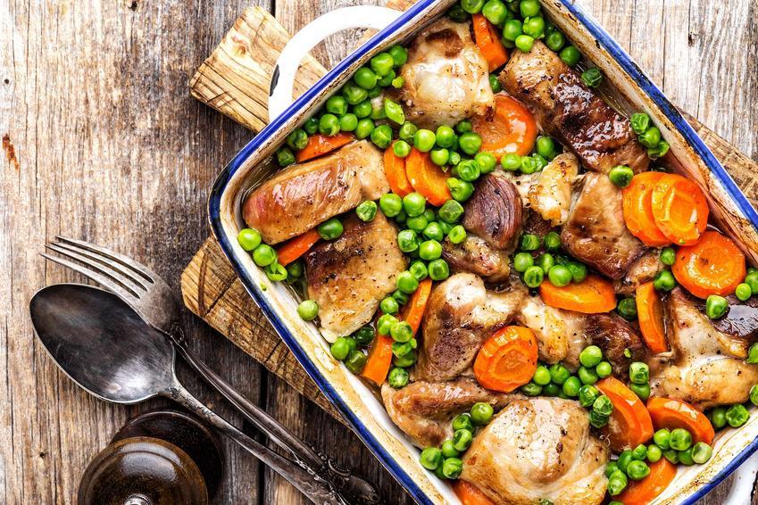 Potrawka z kurczaka z marchewką i groszkiem znajduje się w naczyniu żaroodpornym postawionym na desce do krojenia. Potrawa stoi na blacie stołu, na którym leży łyżka i widelec.