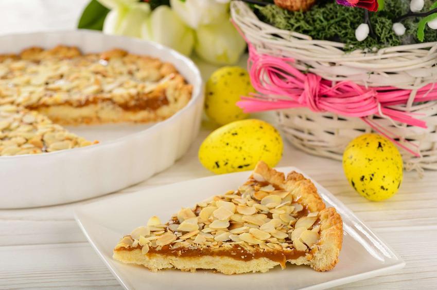 Mazurek kajmakowy podany na talerzyku oraz w blaszce. Całość przyozdobiona jest wielkanocnymi ozdobami.