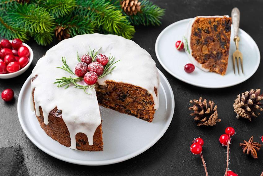 Na zdjęciu widzimy ciasto marchewkowe oblane białą polewą do ciasta marchewkowego. Ciasto znajduje się na talerzu, a dookoła niego leżą szyszki i gałązki świerku.
