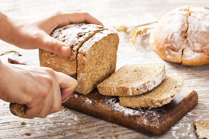 Chleb baltonowski ułożony na desce, częściowo pokrojony.