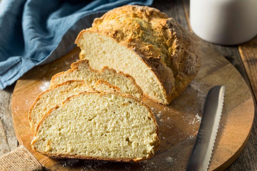 Chleb na sodzie pokrojony na kromki, podany na drewnianej desce.