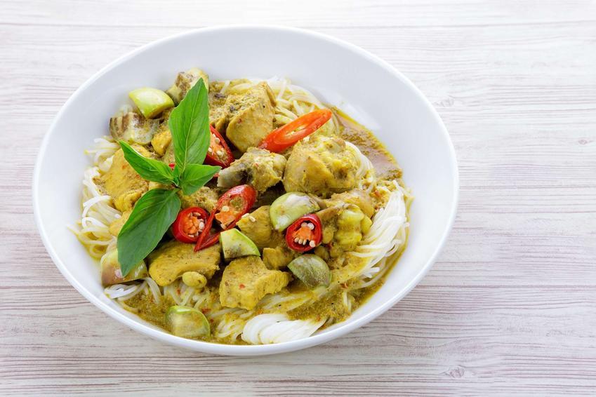 Zielone curry z kurczakiem i makaronem ryżowym podane w głębokim, białym talerzu.