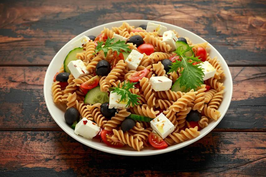 Porcelanowa płaska miska stoi na ciemnych deskach. W miejsce znajduje się makaron fusilli, oliwki, pomidory, ogórki, ser feta oraz zielone dodatki.