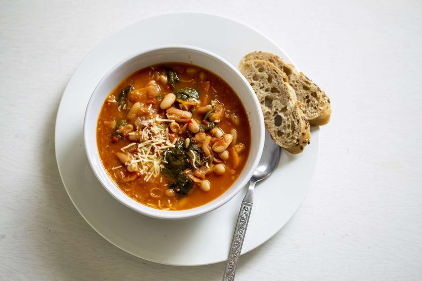 Zupa toskańska podana w eleganckiej miseczce z kromką chleba.