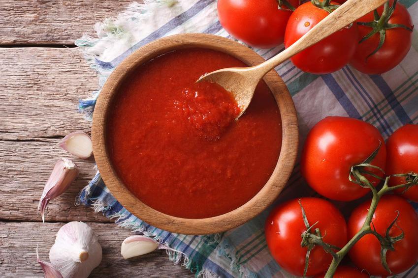 Domowy ketchup znajduje się w drewnianej miseczce. Obok leżą pomidory i czosnek.
