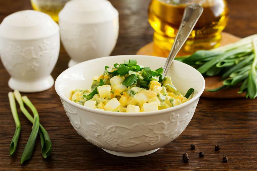 Sałatka z pora i jajka znajduje się w porcelanowej małej misce. Do sałatki włożona jest łyżeczka. Obok leży szczypiorek i ziarenka pieprzu, solniczka, pieprzniczka i naczynie z oliwą z oliwek.