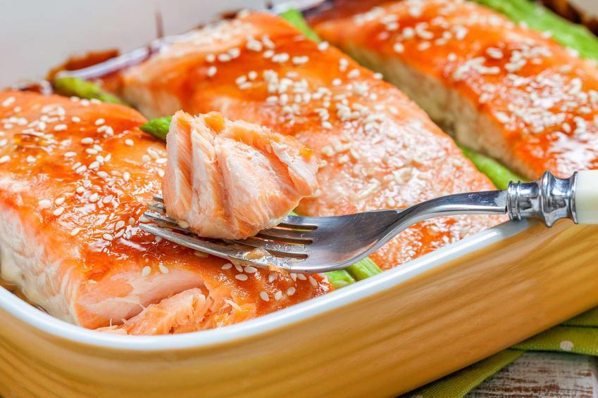 Łosoś teriyaki i szparagi znajdują się w naczyniu żaroodpornym.