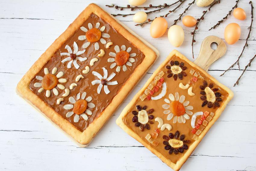 Mazurek pomarańczowy znajduje się na desce do krojenia. Obok leży mniejszy mazurek. Obok ciast porozkładane są jajka i bazie.