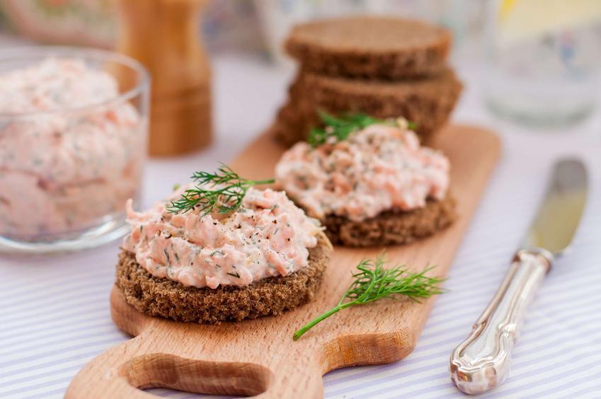 Pasta z łososia znajduje się na ciemnym pieczywie i w szklance. Obok leży nóż. Kanapki z pastą leżą na desce do krojenia.