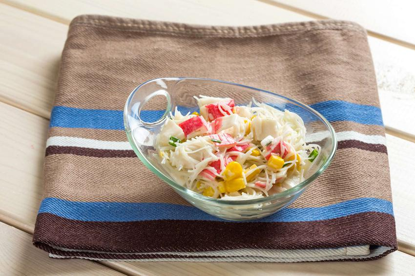 Sałatka krabowa z makaronem znajduje się w małej przezroczystej misce. Widać surimi, makaron ryżowy, kukurydzę i szczypiorek. Miska leży na złożonej ściereczce.