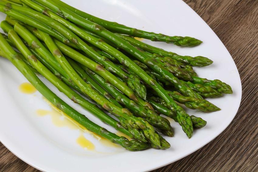 Szparagi na parze na białym półmisku polane oliwą z oliwek.