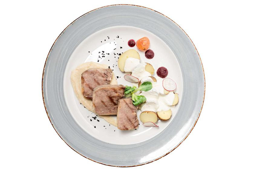 Ozory wieprzowe na eleganckim talerzu z warzywami.