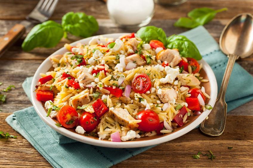 Sałatka z ryżem i kurczakiem, pomidorkami koktajlowymi, papryką czerwoną i cebulą czerwoną znajduje się w głębokim talerzu. Talerz leży na złożonej ściereczce, a obok jest łyżka, widelec oraz liście bazylii.