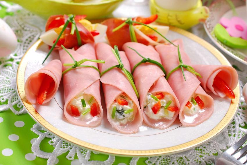 Roladki z szynki konserwowej ułożone na dekoracyjnym talerzu.