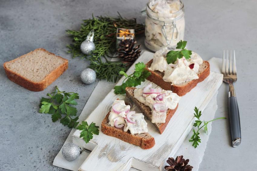 Kanapki ze śledziem z jabłkiem na białej, drewnianej desce do krojenia. Obok znajduje się  natka pietruszki, pieczywo, słoik ze śledziami i ozdoby.
