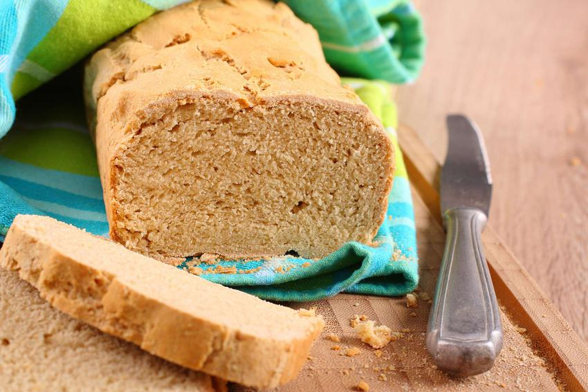 Chleb jaglany z odkrojonymi pierwszymi kawałkami, leży na desce do krojenia i jest zawinięty w ściereczkę kuchenną. Obok chleba leży nóż.