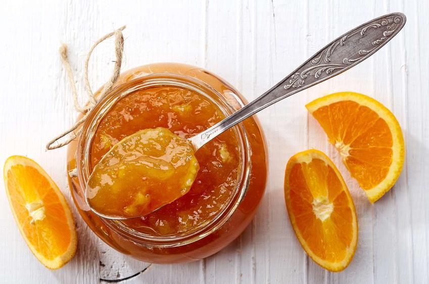 Słoik z konfiturą z pomarańczy na białym blacie. Na słoiku leży łyżeczka z konfiturą, a obok znajdują się pokrojone pomarańcze.