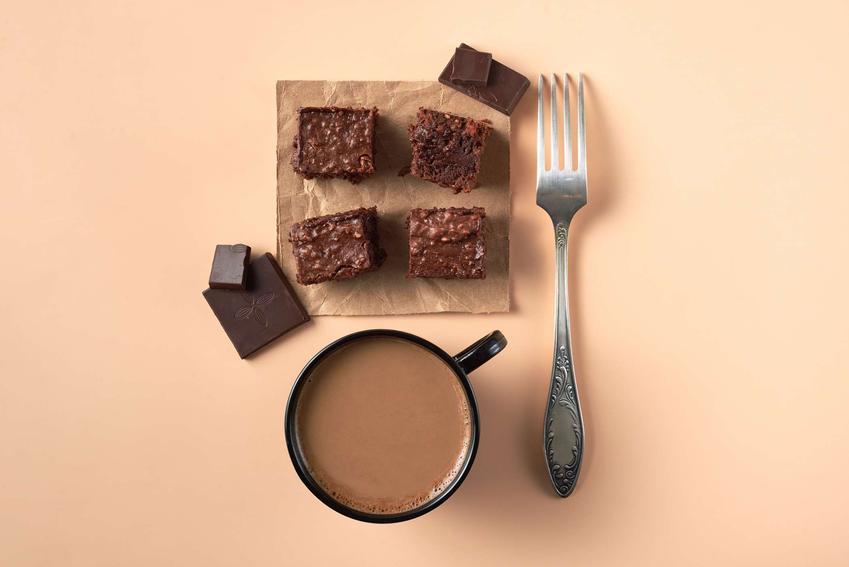 4 kawałki ciasta daktylowego na tekturze. Obok, na różowym tle, leż widelec, kawałki czekolady i kubek kakao.