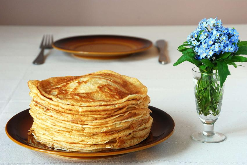 Stos placków naleśnikowych ułożonych na talerzu. Obok niebieskie drobne kwiatki w szklanym wazonie.