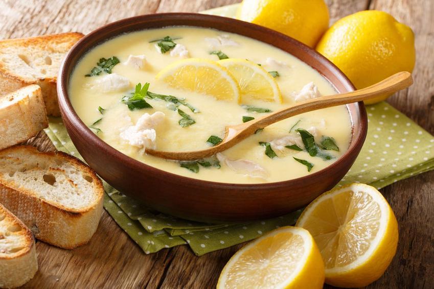 Zupa cytrynowa podana w drewnianej miseczce z plasterkami cytryny i ziołami.