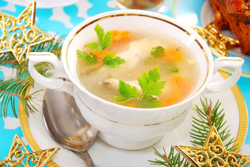Biało-złota miseczka z zupą z karpia na spodeczku. Obok znajdują się złote gwiazdki i gałązki świerku.
