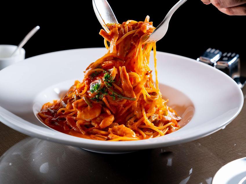 Makaron z marchewki z sosem pomidorowym, na białym, głębokim talerzu. Makaron poniesiony jest do góry przy pomocy widelca i łyżki.