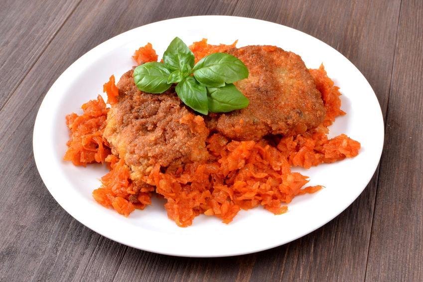 Marchew zasmażana podana na białym talerzu z dodatkiem ryby smażonej.