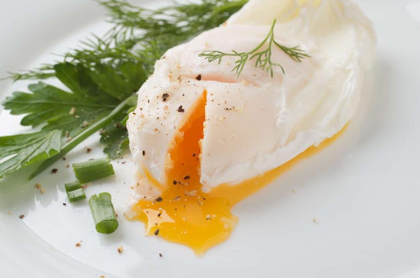Jajka w mikrofali podane na małym białym talerzyku i udekorowane szczypiorkiem.