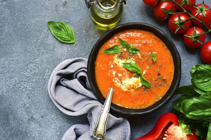 Krem z pomidorów i papryki podany w czarnej misce w towarzystwie warzyw i ziół.
