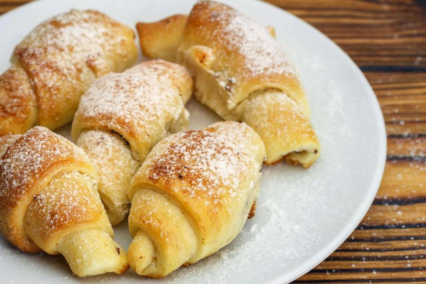 Rogaliki trzyskładnikowe ułożone na białym talerzyku i posypane cukrem pudrem.