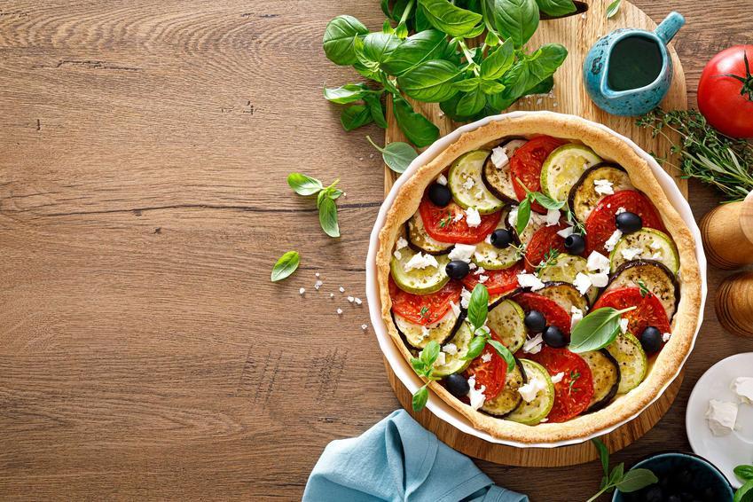 Tarta wytrawna podana na desce, obok świeża bazylia, ściereczka, dzbanuszek, pomidor.