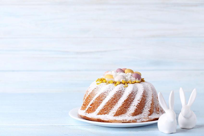 Babka wielkanocna podana na białym talerzu, opruszona cukrem pudrem, udekorowana małymi pisankami, obok dwa białe ceramiczne zajączki.
