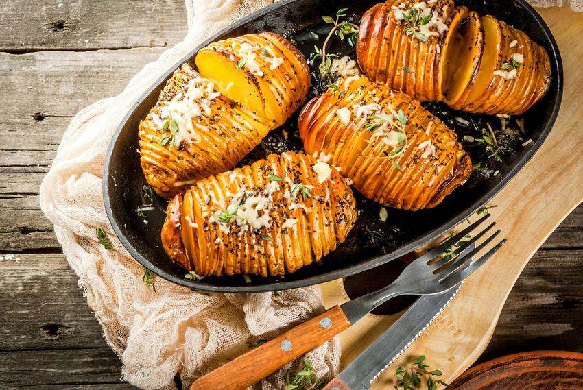 Ziemniaki hasselback podane na czarnym, owalnym talerzu na drewnianej desce i ściereczce