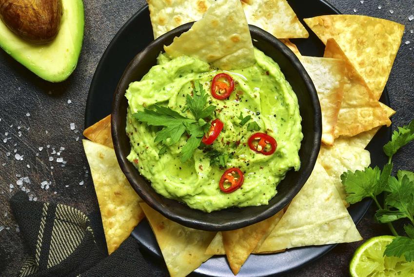 Guacamole podane w czarnej miseczce z chipsami.