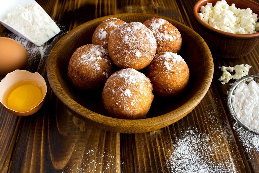 Pączki bezglutenowe znajdują się w drewnianej misce. Obok ustawione są składniki na te pączki (twaróg, jajko, mąka, cukier puder).