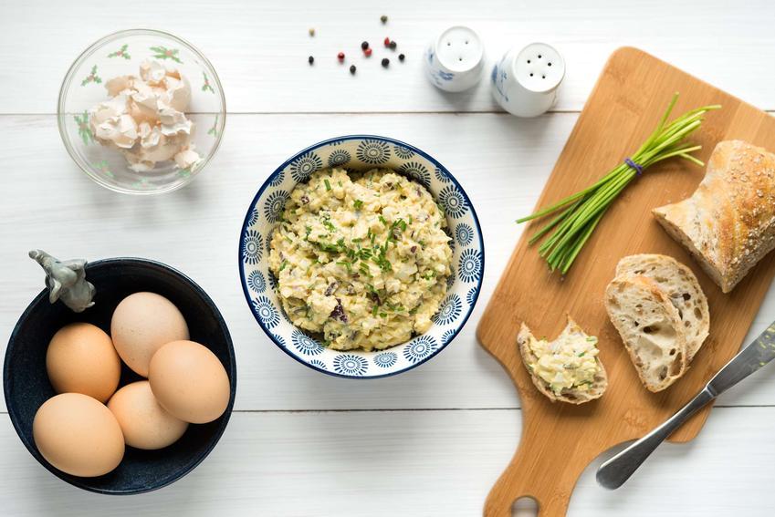 Pasta jajeczna z twarogiem znajduje się w misce. Obok stoi miska z jajkami, miska z twarogiem oraz pieprzniczka i solniczka. Na desce do krojenia leży chleb oraz szczypiorek.