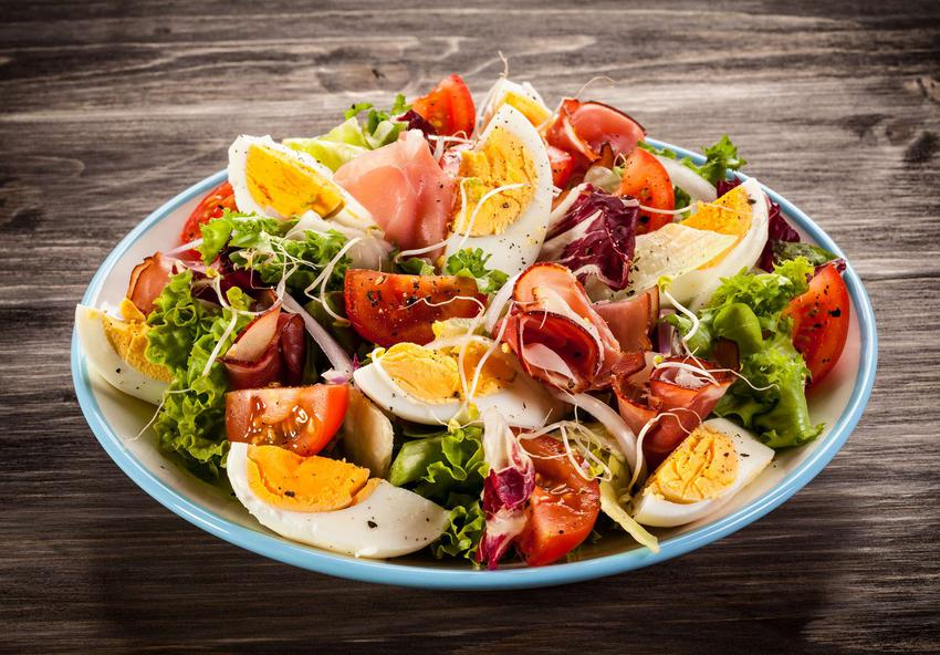 Sałatka z jajkiem i szynką parmeńską, pomidorkami koktajlowymi, sałatą karbowaną leży na biało-niebieskim talerzu.