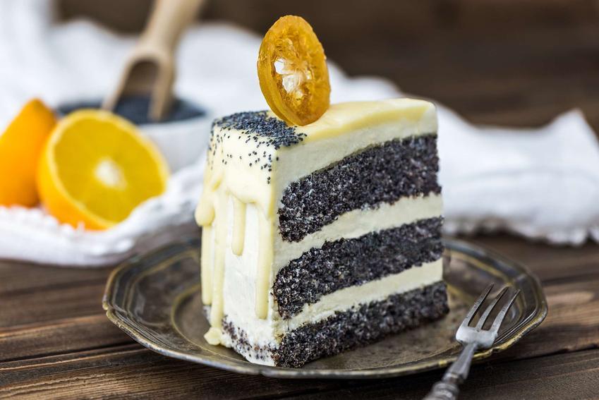 Tort makowy podany na małym, ciemnym talerzyku, na drewnianym stole. W tle biała ściereczka z dwoma połówkami pomarańczy i miseczką maku.
