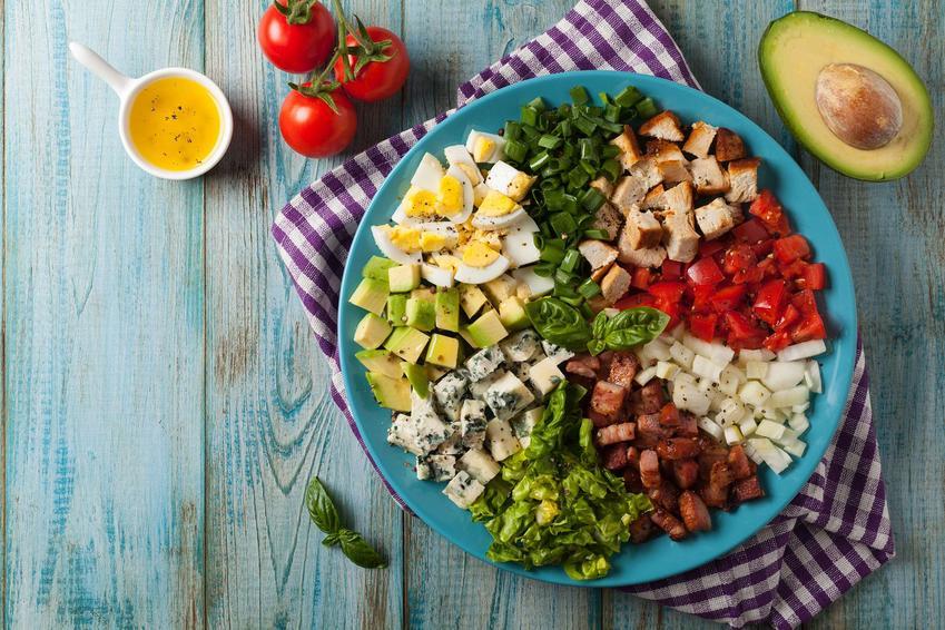 Sałatka Cobb z jajek, awokado, niebieskiego sera, boczku, kurczaka, pomidorków, szczypiorku, grzanek, sałaty i cebuli znajduje się na niebieskim dużym talerzu. Obok leży przekrojone awokado, pomidorki koktajlowe i sos winegret. Talerz leży na ściereczce.