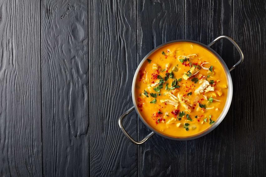 Zupa gyros podana w garnku stojącym na drewnianym blacie.