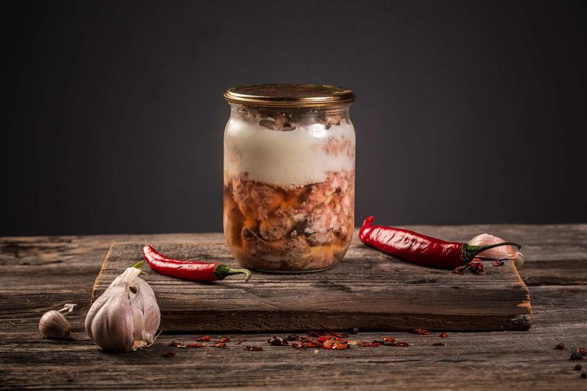 Kiełbasa słoikowa podana w szklanym słoiku, który stoi na drewnianym blacie.
