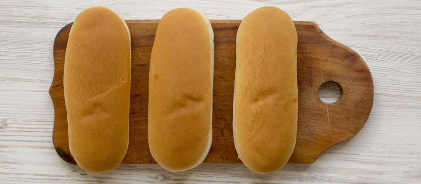 Bułki do hot-dogów podane są na drewnianej desce do krojenia.
