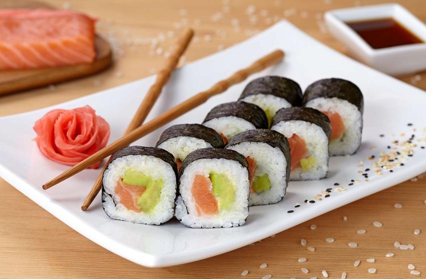 Sushi z łososiem na białym, porcelanowym talerzu. Obok znajdują się pałeczki, róża z plastrów łososia i rozsypany sezam. Z tyłu leży kawałek łososia i miseczka z sosem.