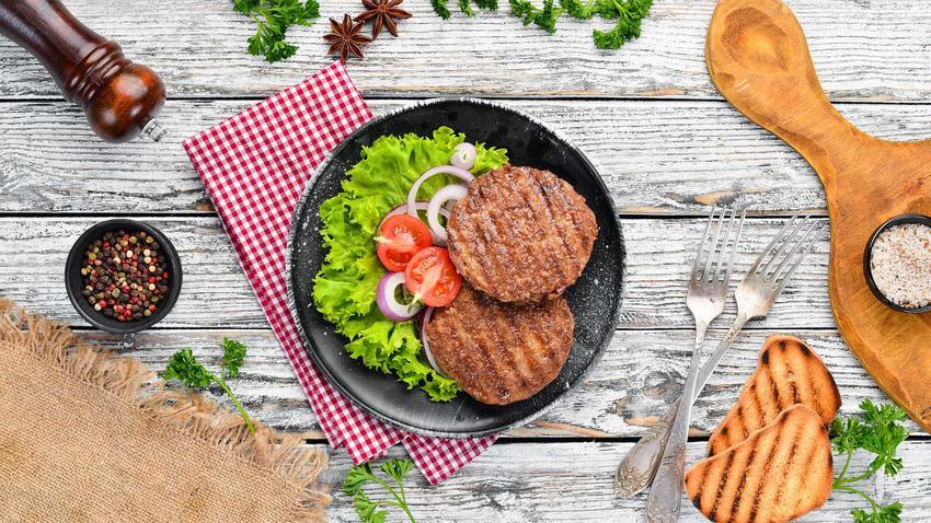 Steki z cebulką na czarnym talerzu z warzywami. Talerz leży na białym, drewnianym stole i biało-czerwonej ściereczce. Obok znajduje się zgrillowane pieczywo, przyprawy i sztućce.
