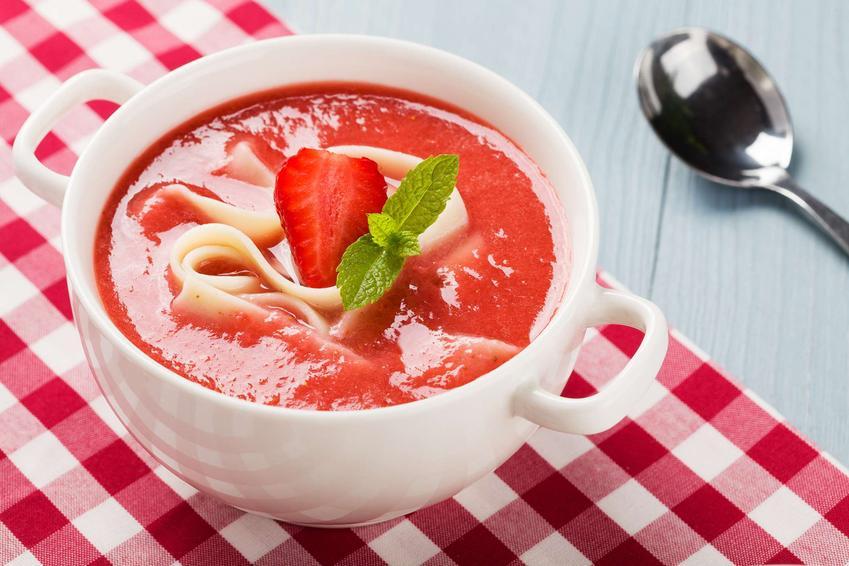 Biała miseczka z zupą truskawkową z makaronem. Miseczka stoi na biało-czerwonej ściereczce, a obok leży łyżka.