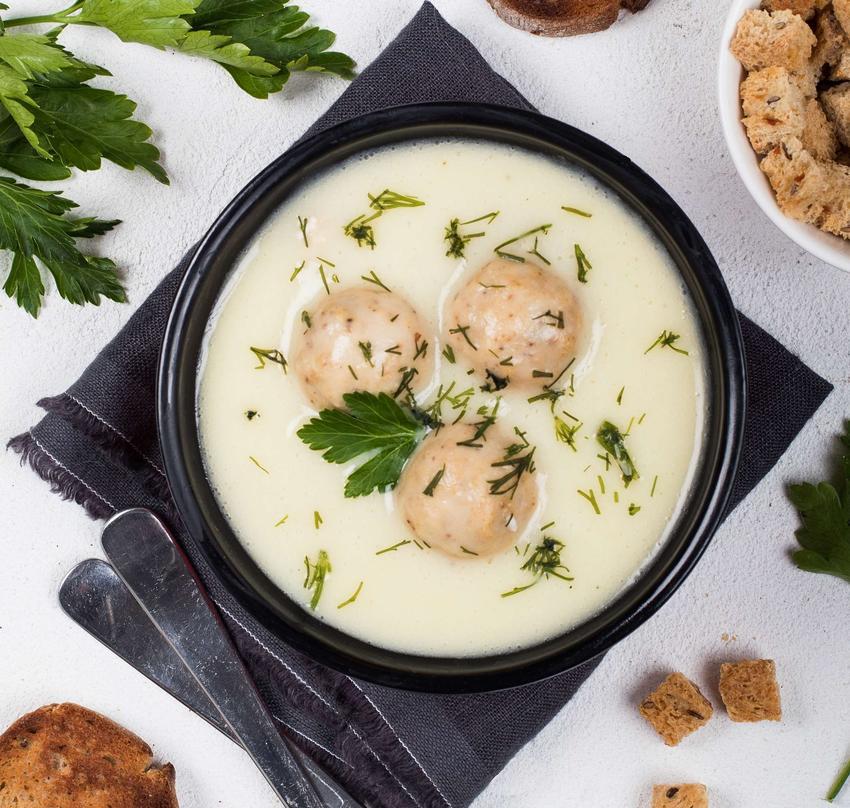 Czarna miska z zupą serową z pulpecikami, na czarnej ściereczce. Obok znajdują się sztućce, natka pietruszki i grzanki.