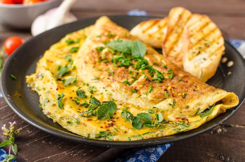 Omlet z serem podany na eleganckim talerzu i posypany szczypiorkiem.