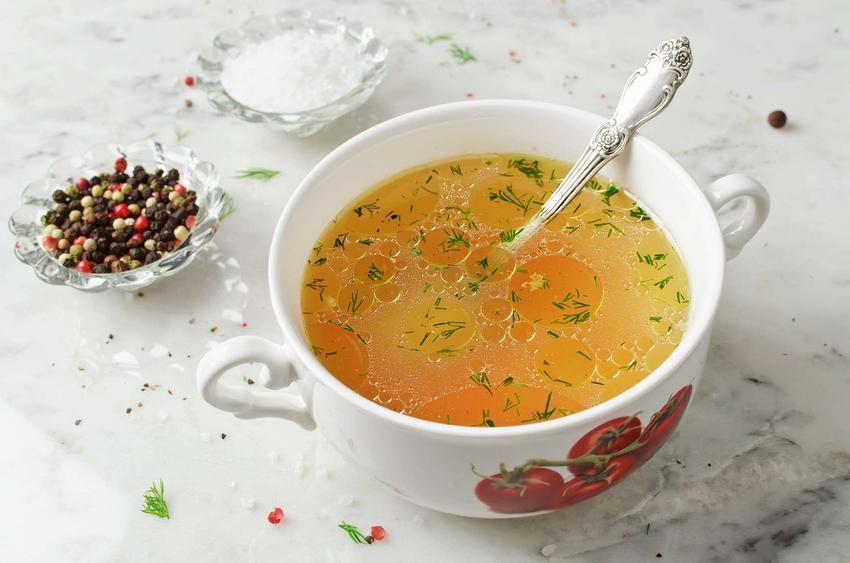 Rosół z bażanta w białej miseczce z obrazkiem pomidorów. W misce z rosołem znajduje się łyżka. Z tyłu stoją pojemniczki z przyprawami.