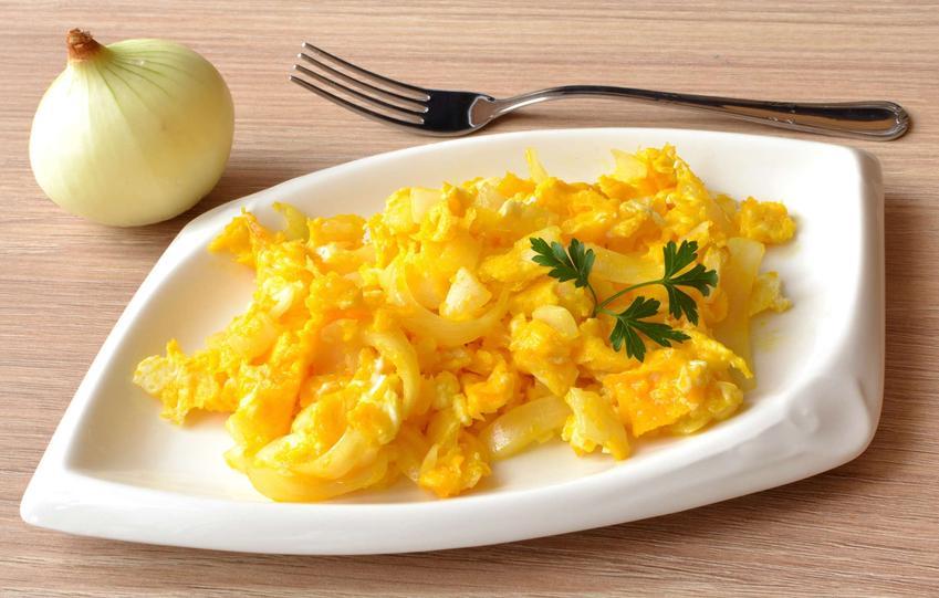 Jajecznica z cebulą na białym talerzu, obok którego leży widelec i świeża cebula.