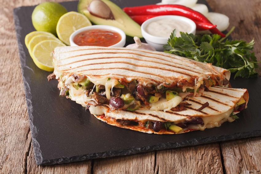 2 quesadille z mięsem mielonym na czarnej, kamiennej tacy. Za quesadillami leżą limonki, sosy, awokado i warzywa.